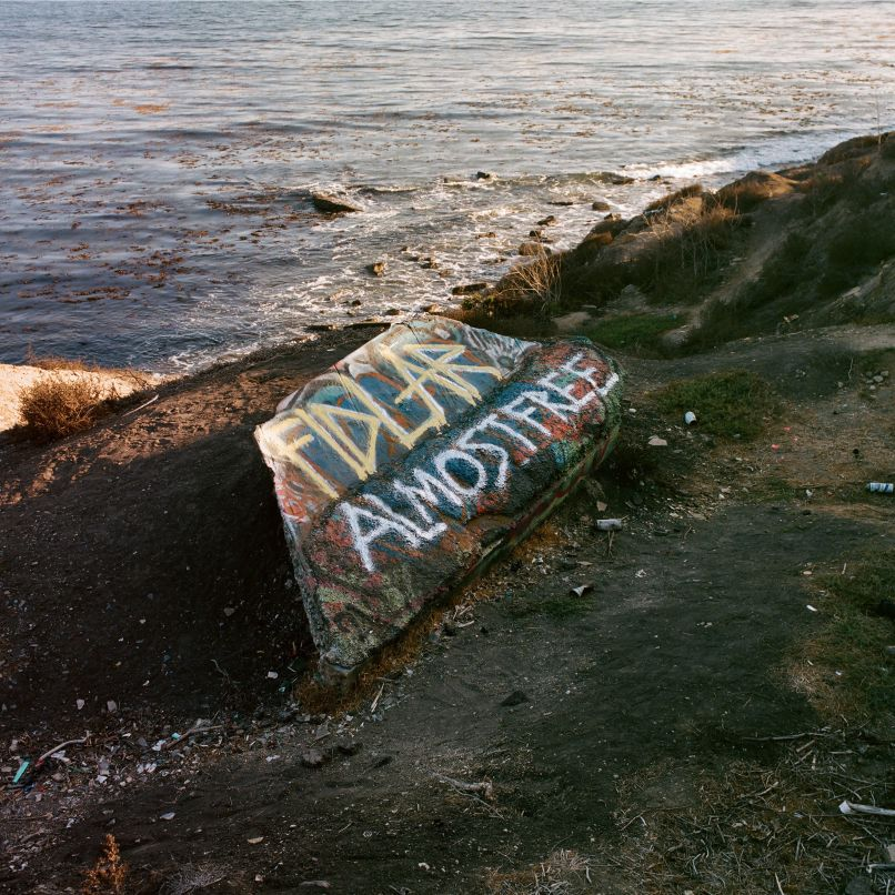 FIDLAR Almost Free album cover graffiti writing on a concrete block by a beach