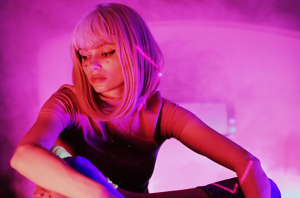 Photo of Winona Oak in a pink wig looking away from the camera against a background lit with pink lights