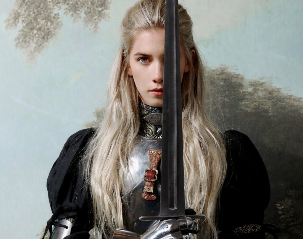 Woodes wears a suit of armour and holds a sword that covers half her face